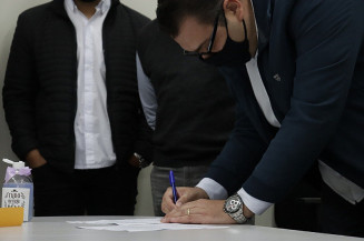 Alan Guedes assinando comprovante de doações (Imagem: Assecom)